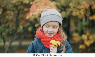funny little girl holding a small bouquet and enjoy the...