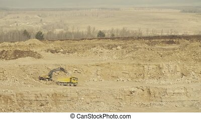 Truck loading in a quarry. Truck and excavator