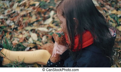 cute little girl playing with her teddy bear hugs and holds it to her sitting on the grass in autumn park 4k
