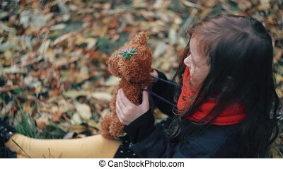 cute little girl playing with her teddy bear hugs and holds it to her sitting on the grass in autumn park