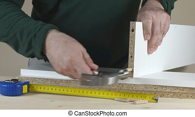 Placing Wooden Dowels - Man placing wooden dowels into a...