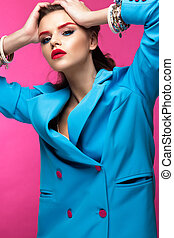 Beautiful girl in blue suit on pink background with creative...