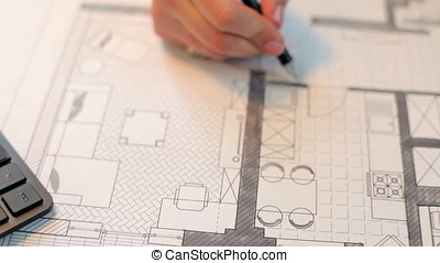 Architect woman working on blueprints at her desk
