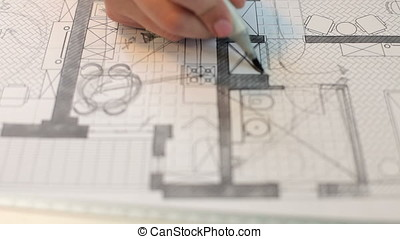 Following hands of architect woman making changes to blueprints