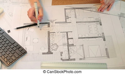 Architect woman making notes on blueprints at her desk....