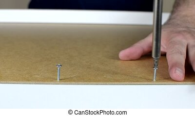 Screwing of Two Bolts - Close-up of assembling a drawer, by...
