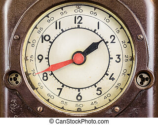 Close up of a vintage brown bakelite clock with red minute...