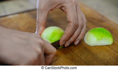 Woman with knife cutting onion in the kitchen.