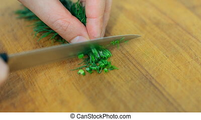 Woman with knife cutting dill in the kitchen.