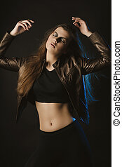 Fashionable young woman with fluttering hair posing at studio with blue light