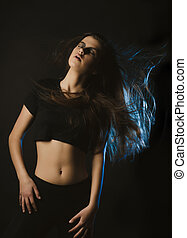 Sensual young woman with fluttering hair posing at studio with blue light