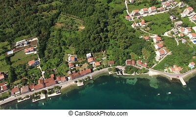 City sandy beach with a pier and coastal dwelling houses in the town of Petrovac. Aerial view