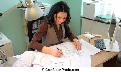 Business woman at her office working on blueprints