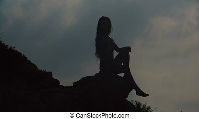 silhouette of young woman with long hair on sky background