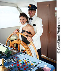 Newlyweds at the Helm - Bride and groom smiling as they...