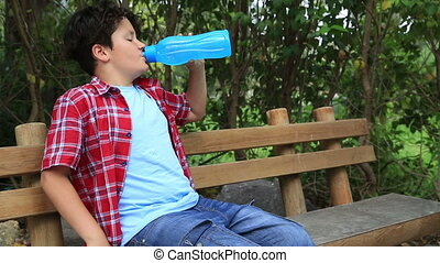 Young boy driking water from plastic bottle