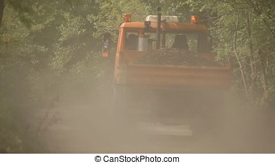 Orange Truck Stirring Up Dust on Gravel Wood Road - Orange...