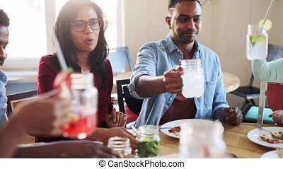 friends eating and clinking glasses at restaurant - leisure,...
