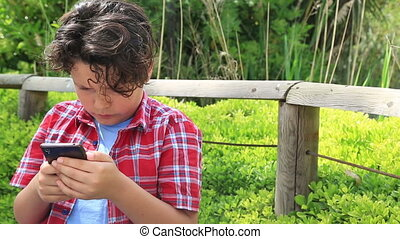 Young boy with smartphone - Young boy playing with mobile...