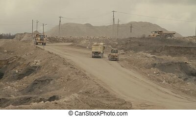 Four trucks and excavator on a road in quarry, day country...