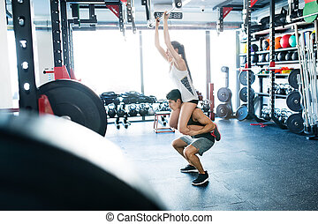 Woman in gym doing pull ups, man giving her piggyback.