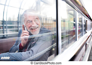Senior man with smartphone in glass passage making phone...