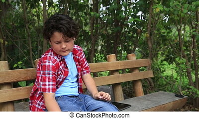 Child scratching his self at park - Young boy scratching his...