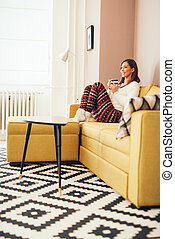 Leisure Activity - Beautiful young woman resting at living...