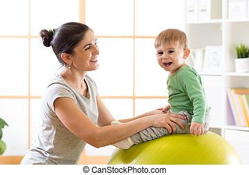 Happy mother with baby son doing gymnastics on the big fitness ball in the gym.
