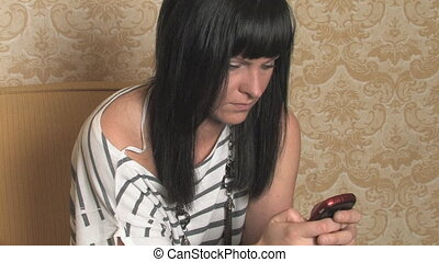 Young woman texting - Young woman uses her phone to read and...