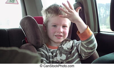 Cute boy in a child car seat smiles and laughs - Little cute...