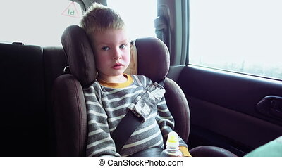 Cute boy in a child car seat plays with a toy - Little cute...
