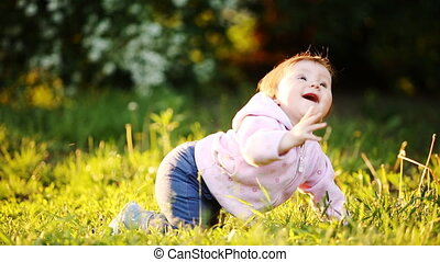 Little cute baby learning to crawl on the green grass in the...