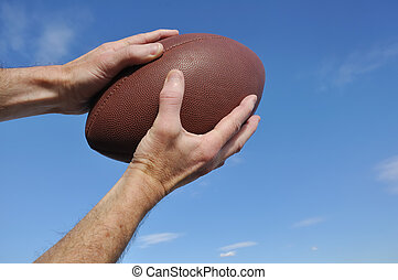 Receiver Catching an American Football Pass Against a Blue...