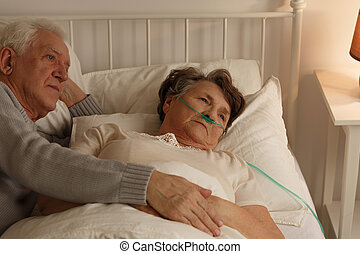 Lying next to dying wife - Man lying on bed next to elderly...
