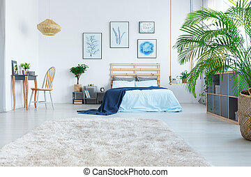 Stylish bedroom with wooden bed, dressing table and plant