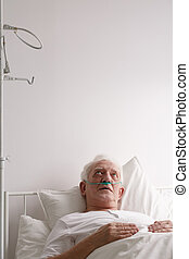 Patient staring at hospital ceiling - Worried elderly male...