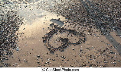 heart in sand on the sea shore in Sunny day