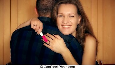 Happy couple with pregnancy test hugging at home. Positive...