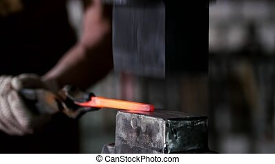 Blacksmith forging red hot iron on anvil - automatic...