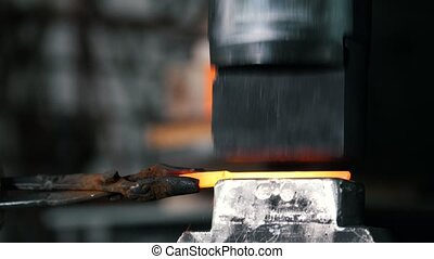 Automatic hammering - blacksmith forging red hot iron on...