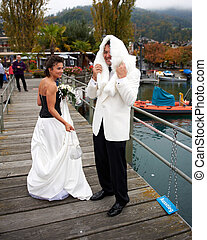 Smiling Bride And Groom - A smiling bride and groom are on a...