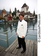 Smiling Groom - A smiling groom is on a pier in front of a...