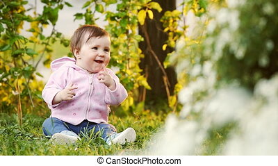 Cute smiling baby seating on the green grass in the park at...