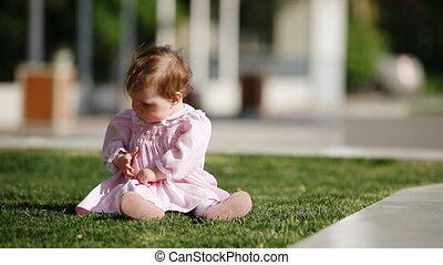 Happy baby-girl seated on the green grass in the park and playing.