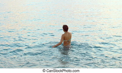 beautiful tanned woman with long hair coming out of water -...