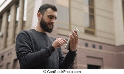 Happy beard young man using tablet computer in the street at...