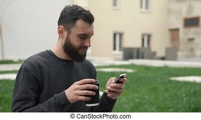 Happy beard young man texting on smartphone and drinking coffee in the street at sunset