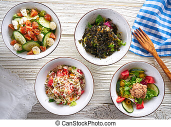 four salad mix bowls healthy food on white wood table