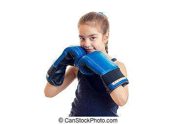 little girl smiling and holding hands in a large adult boxing gloves near individuals